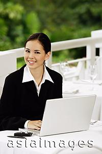 Asia Images Group - Businesswoman sitting with laptop, looking at camera