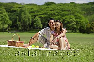 Asia Images Group - Couple sitting in park, having a picnic, looking at camera
