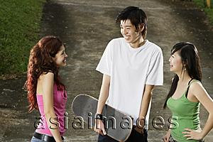 Asia Images Group - Three teenagers talking, young man holding skateboard