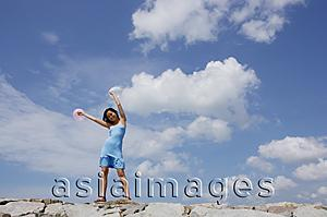 Asia Images Group - Woman standing on breakwater, waving balloons in air