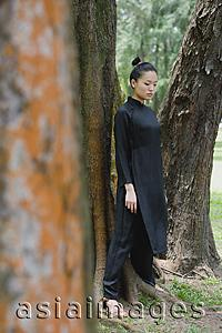 Asia Images Group - Young woman in traditional Chinese costume, standing amongst trees