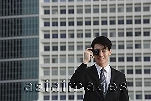 Asia Images Group - Businessman using camera phone