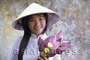 Asia Images Group - Young woman wearing traditional Vietnamese outfit holding Lotus flowers