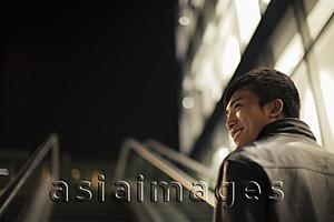 Asia Images Group - Rear view of young man going up an escalator at night
