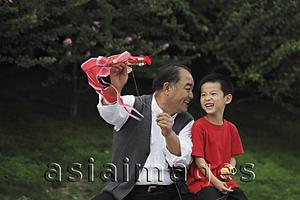 Asia Images Group - Grandfather and grandson playing with a kite