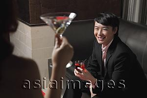 Asia Images Group - Young woman looking at young man holding a drink and smiling