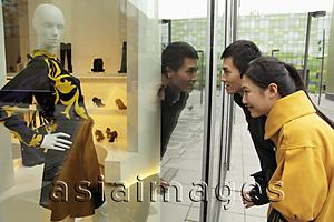 Asia Images Group - Young couple looking in shop window while shopping