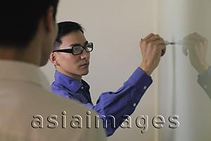 Asia Images Group - Man writing on white board while another looks on
