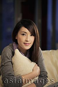 Asia Images Group - Young woman holding a pillow and smiling