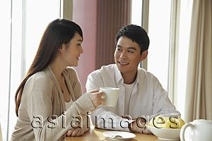 Asia Images Group - Young couple drinking coffee together in their home
