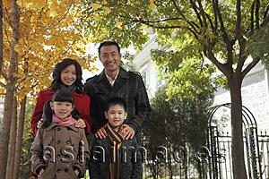 Asia Images Group - Family of four standing together in front of their house