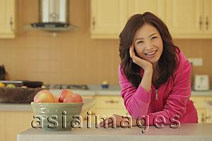 Asia Images Group - Young woman wearing pink smiling in her kitchen