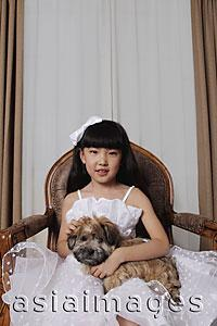 Asia Images Group - Young girl dressed up in white dress holding a puppy