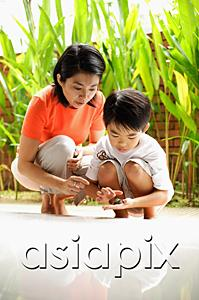 AsiaPix - Mother and son crouching, son holding terrapin