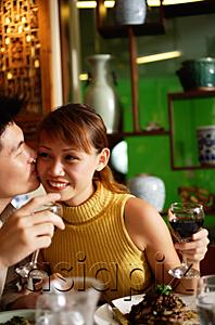 AsiaPix - Man kissing woman on cheek in restaurant