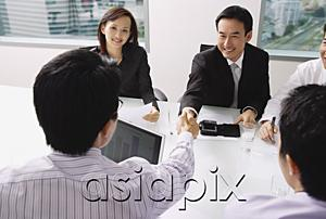AsiaPix - Businessmen in meeting, shaking hands across table