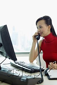 AsiaPix - Female executive sitting at office desk, using telephone