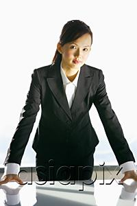 AsiaPix - Businesswoman leaning on table, looking at camera