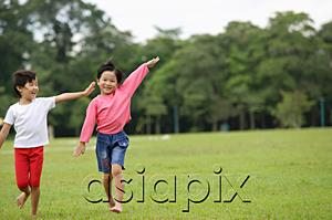 AsiaPix - Two girls running on grass, side by side, arms outstretched