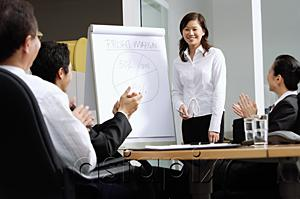 AsiaPix - Businesswoman standing next to flipchart, colleagues sitting and clapping