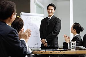 AsiaPix - Businessman standing next to flipchart, other executives clapping
