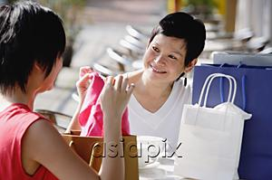 AsiaPix - Two women at cafe, looking at items from their shopping bags