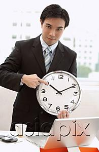 AsiaPix - Businessman holding and pointing at clock