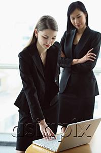 AsiaPix - Two women standing in front of laptop