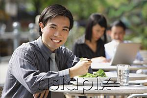 AsiaPix - Businessman having lunch at outdoor cafe, smiling at camera