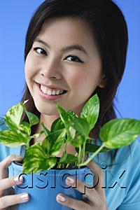 AsiaPix - Young woman holding plant pot