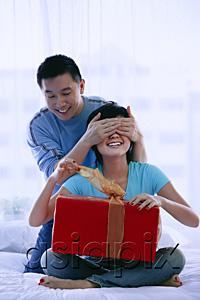 AsiaPix - Couple in bedroom, woman opening gift, man covering her eyes