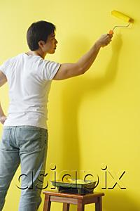 AsiaPix - Man painting wall with yellow paint