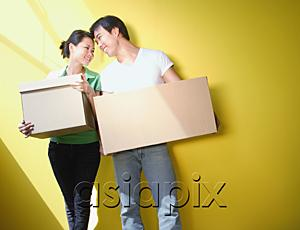 AsiaPix - Couple carrying boxes, standing against yellow wall