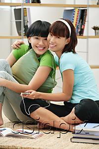 AsiaPix - Young women listening to MP3 player, smiling at camera