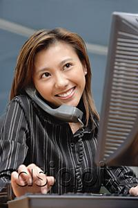 AsiaPix - Female executive at desk, using computer and telephone, smiling