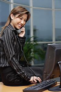 AsiaPix - Businesswoman sitting on desk, using telephone
