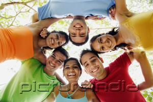 PictureIndia - Group of young adults arms around each other, looking down at camera