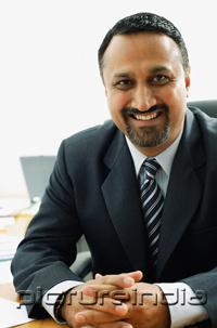 PictureIndia - Businessman at desk, looking at camera, smiling