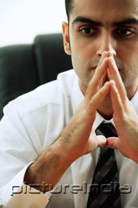 PictureIndia - Businessman with hands together, looking away