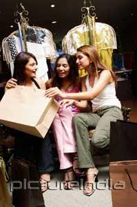 PictureIndia - Three women sitting in clothing store, looking inside shopping bag