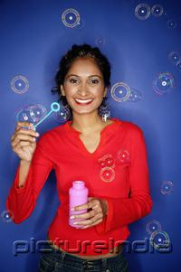 PictureIndia - Woman holding bubble wand, bubbles around her