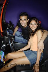 PictureIndia - Couple in a video game arcade, smiling at camera