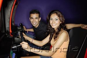 PictureIndia - Couple in a video game arcade, playing games, smiling at camera