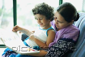 PictureIndia - Daughter sitting on mothers lap, reading a book