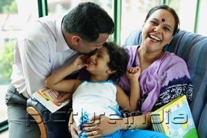 PictureIndia - Family with one child, father kissing daughter's head, mother smiling at camera