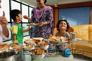 PictureIndia - Family of four having a meal at home, mother feeding son