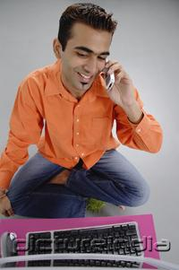 PictureIndia - Man sitting in front of laptop, using mobile phone