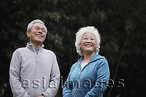 Asia Images Group - A senior couple in sweatsuits laughing outdoors